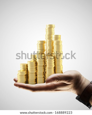 hand holding gold coins city on gray background - stock photo