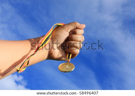 hand holding gold medal on blue sky - stock photo