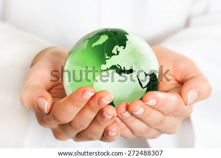 Hand holding green glass globe - stock photo