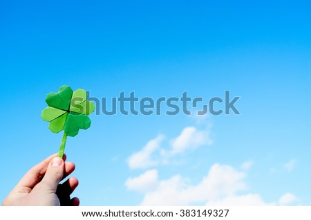Hand holding green paper origami folded shamrock on blue sky background. Sunny weather outdoors. Space for text, lettering, copy. - stock photo