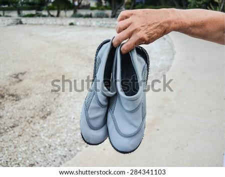 Hand holding grey water swim shoes the beach - stock photo