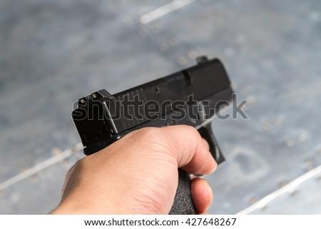 Hand holding gun - stock photo