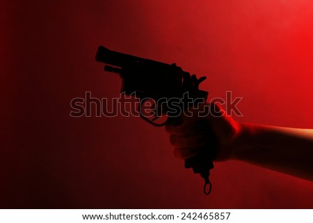 Hand holding gun on red background - stock photo