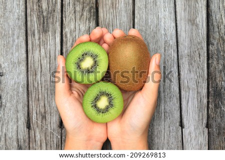Hand holding half kiwi fruits on wooden table background - stock photo