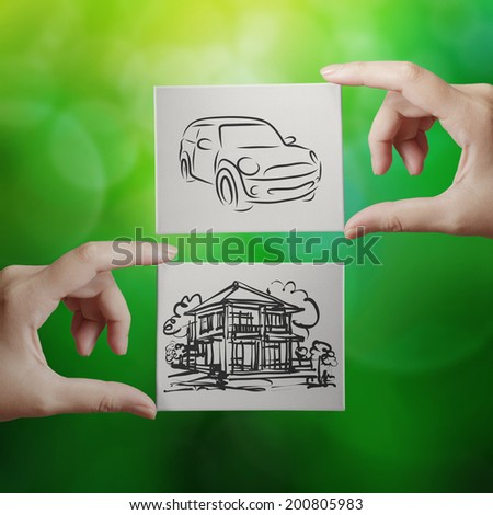 hand holding hand drawn house and car on canvas board on nature background as concept  - stock photo