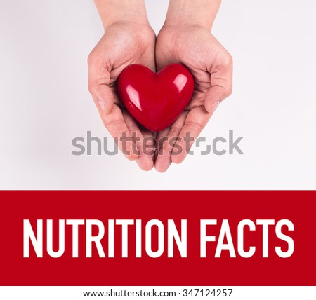 Hand holding heart shape with NUTRITION FACTS text - stock photo