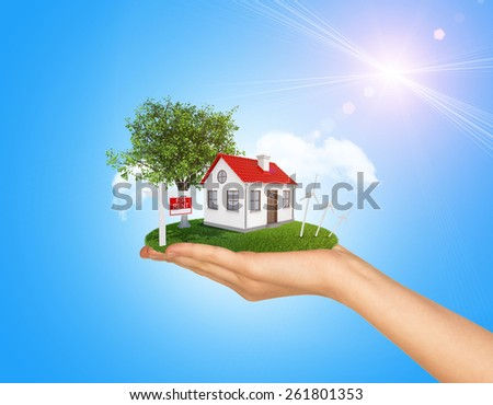 Hand holding house on green grass with red roof, chimney, tree, wind turbine. Near there is signboard for rent. Background clouds and blue sky - stock photo