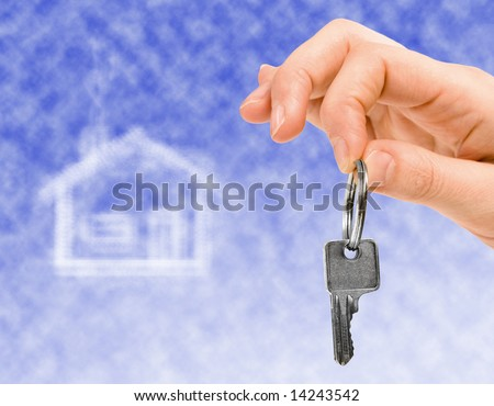 hand holding key of a property over a blue sky. house made of clouds on background.  Dream house. - stock photo