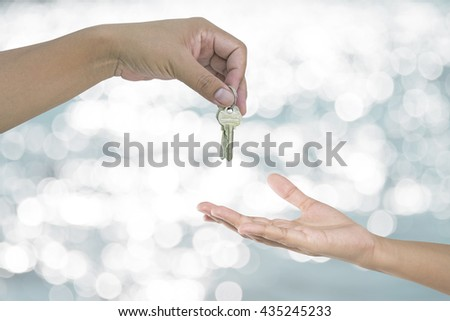 Hand holding key on abstract blurred background - stock photo