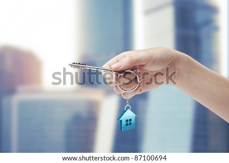 Hand holding key with a keychain in the shape of the house. House key - stock photo