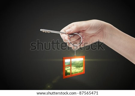 Hand holding key with a keychain in the shape of the window. Beautiful view behind a window of a green field with a blue sky. House key on a black background - stock photo