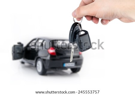 Hand holding keys to new car. Buy or selling business composition - stock photo