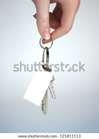 Hand holding keys with key chain having room for text ,graphic or copy space. Vehicle ownership , insurance,service ect. Gradient background - stock photo