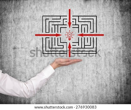 hand holding labyrinth on gray wall background - stock photo