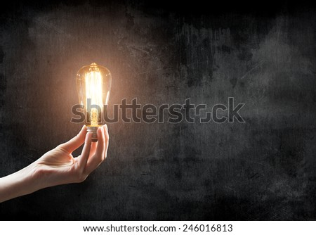hand holding Light bulb on blackboard background  - stock photo