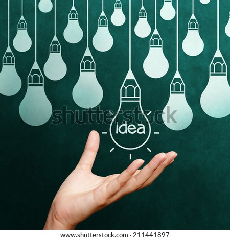 hand holding Light bulb on blackboard background as concept - stock photo