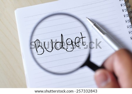 """Hand Holding Magnifying Glass on Note Book with Pen Write """"BUDGET"""", Focus on Note Book  - stock photo"""