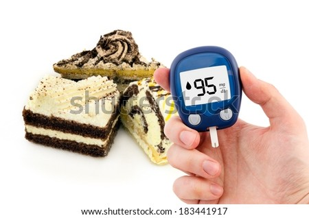 Hand holding meter. Diabetes doing glucose level test. Cake in background - stock photo