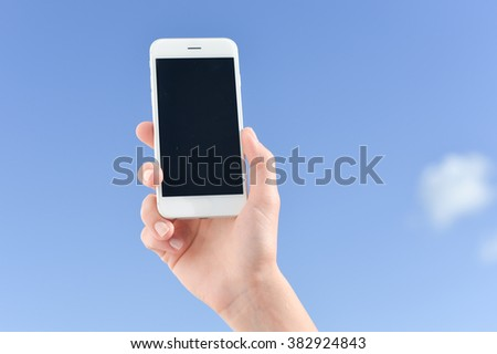 Hand holding mobile cell phone on sunny light blue sky outdoors background. Video photo on the move - stock photo