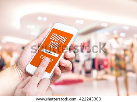 Hand holding mobile phone with coupon code word with blurred store background with bokeh light ,internet marketing concept,E-commerce - stock photo