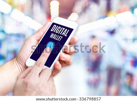 Hand holding mobile phone with Digital Wallet word with blurred supermarket background,Digital marketing concept - stock photo