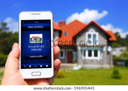 hand holding mobile phone with house sale offer - stock photo