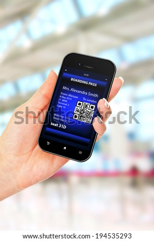hand holding mobile phone with mobile boarding pass on airport - stock photo