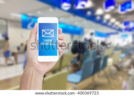 Hand holding mobile phone with New message on blur hospital background - stock photo