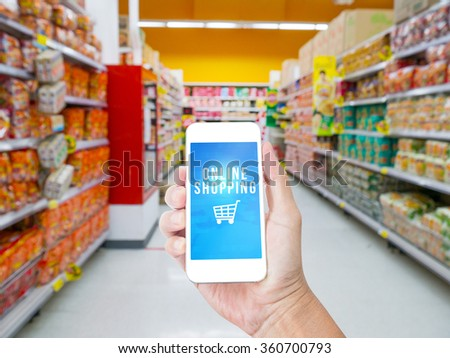 Hand holding  mobile phone  with Online shopping word with blur suppermarket  background,Business solution concept - stock photo