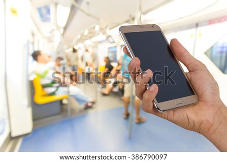 Hand holding mobile smart phone  blurred people standing in sky train. - stock photo