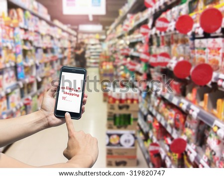 hand holding mobile smart phone shopping online on Supermarket blur background,,business and modern lifestyle concept - stock photo