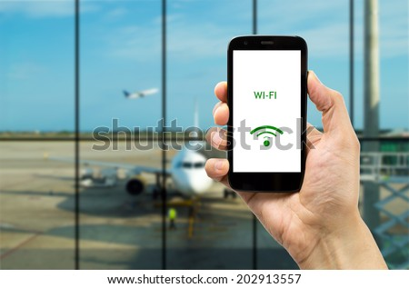 Hand holding mobile smart phone with connect wifi on the airport - stock photo