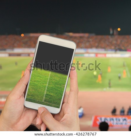 Hand holding mobile smart phone with football stadium, blur image of a football field as background. - stock photo
