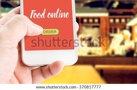 Hand holding mobile with Order food online with blur restaurant background, food online business concept - stock photo