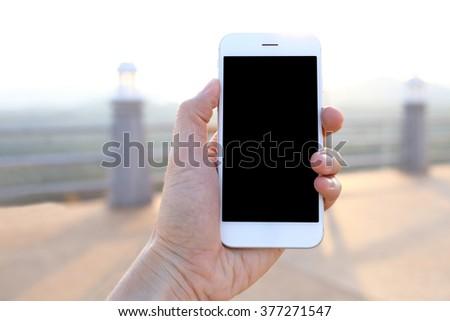 Hand holding mockup smartphone - stock photo