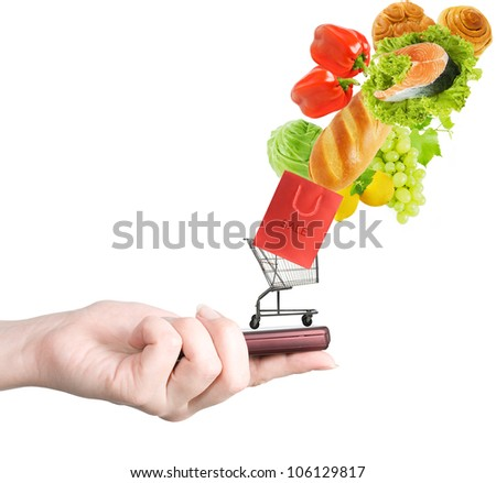 Hand holding modern mobile phone and food flying to shopping cart isolated on white background - stock photo