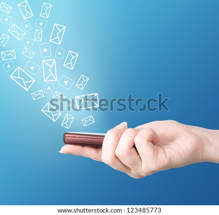Hand holding modern mobile phone, video and letter symbols flaying away. Social media concept - stock photo