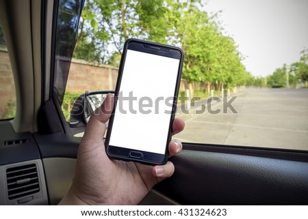 Hand holding modern smartphone with blank screen with copy space for text or design, close-up of male driver hands using mobile phone with car inside background - stock photo