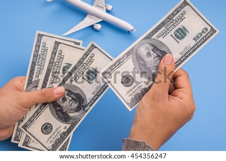 hand holding money and airplane model, blue background, budget travel concept. - stock photo