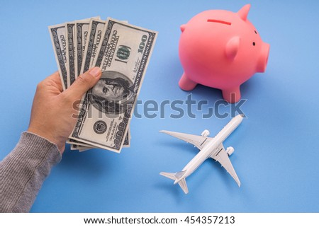 hand holding money and piggy coin saving, blue background, budget travel concept. - stock photo