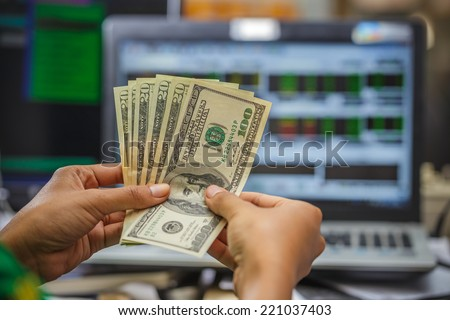 hand holding money with laptop display of stock market on background - stock photo