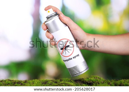 Hand holding mosquito spray on nature background - stock photo