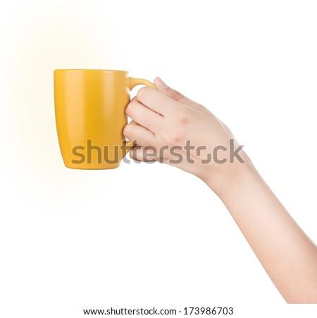 Hand holding mug isolated on white. - stock photo