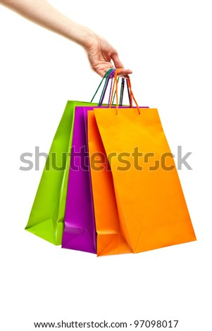 Hand holding multicolored paper bags isolated on white; shopping concept - stock photo