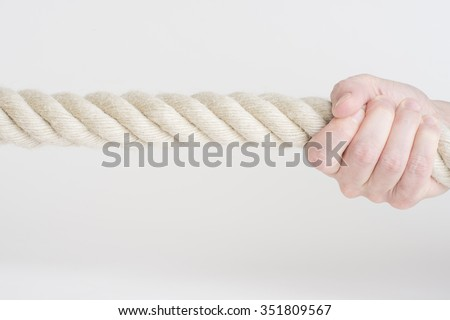Hand holding nautical rope in close-up. Symbol of power, strength and effort. - stock photo