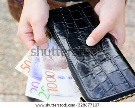 Hand holding new swedish bank notes and wallet. NOTE: the new 2015 model. - stock photo
