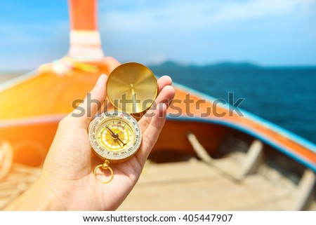 Hand holding old compass on wooden boat in the sea - stock photo