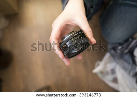Hand holding old type manual prime lens 50 mm on dark background - stock photo