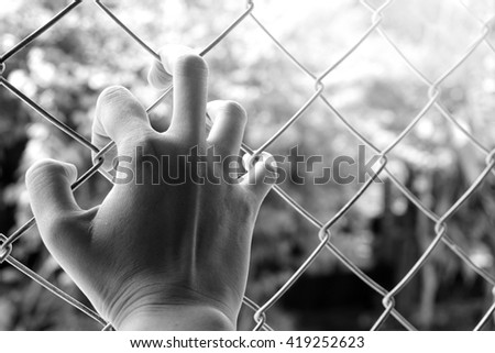 Hand holding on chain link fence in black and white background, sadness or freedom concept - stock photo