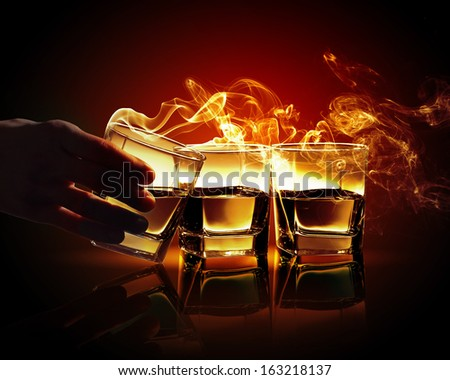Hand holding one of three glasses of yellow absinth with fume going out - stock photo